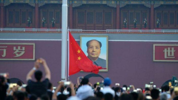 Una fotografía de Mao Zedong a las puertas de la Ciudad Prohibida en Pekín, frente a una multitud de personas con celulares.