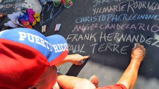 Un hombre escribe los nombres de las víctimas de Orlando con una tiza en el pavimento.