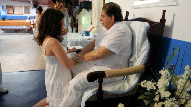 Fotografia de 2012 mostra mulher ajoelhada diante de cadeira onde está sentado João de Deus; ele segura suas mãos com os dois braços
