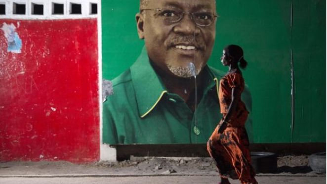 A woman walks past an election billboard of John Magufuli 29 October 2015