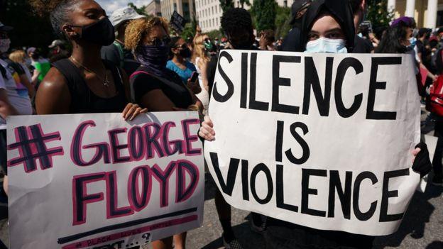 متظاهرون يحملون لافتات احتجاج