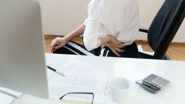 Mujer en silla con dolor de espalda