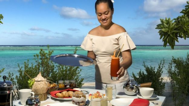 Garçonete servindo comida e bebidas no resort de luxo The Brando