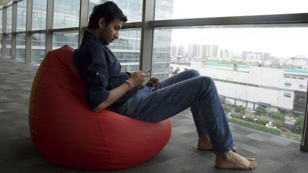 Ritesh Agarwal sitting on a beanbag by the window of the office