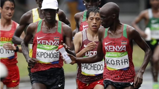 Wesley Korir, of Kenya, right, hands a bottle of water to eventual winner Eliud Kipchoge, also of Kenya, in the men