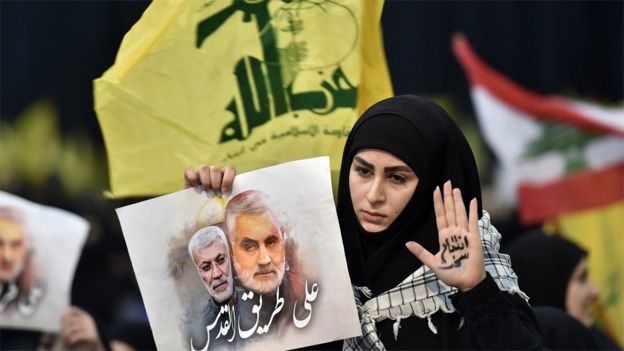 Hezbollah supporter holds up a photo of Abu Mahdi al-Muhandis and Qasem Soleimani at a rally in Beirut, Lebanon (5 January 2020)
