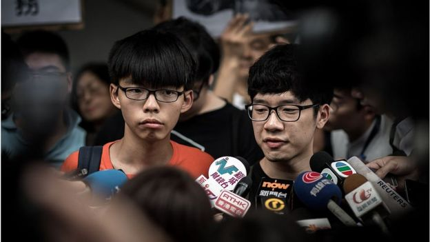 Student protesters Joshua Wong (L) and Nathan Law (C) talk to the media outside the Wanchai police station in Hong Kong on 27 August 2015