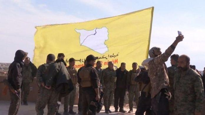 Combatentes sírios erguem bandeira amarela para celebrar derrota do EI