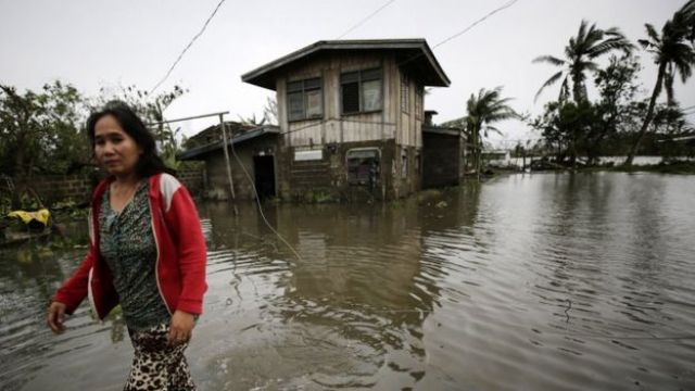 A Filipino villager wades through flood water in the typhoon-hit town of Baggao