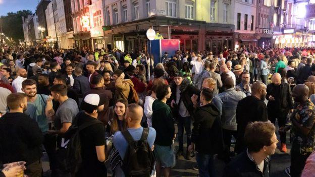 Pessoas bebem na rua no Soho, em Londres