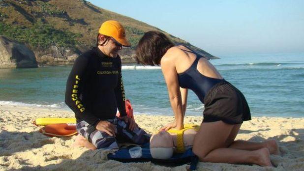 Mulher e salva-vidas simulam manobra com boneco em uma praia