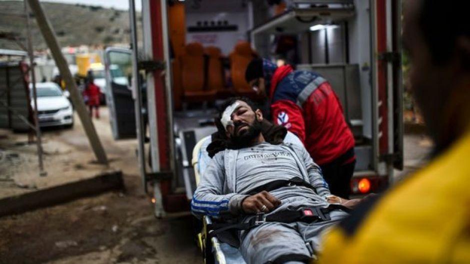 Un herido es montado en una ambulancia.