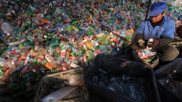 A worker sorts through various plastic bottles collected at a recycling collection centre in Hefei, east China's Anhui province