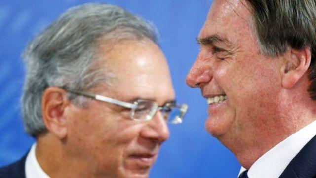 O ministro da Economia, Paulo Guedes, e o presidente Jair Bolsonaro aparecem de perfil sorrindo