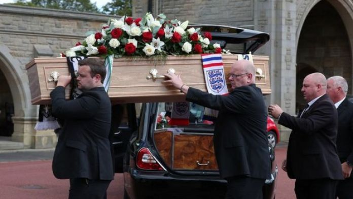 The coffin is carried into the service at West Road Crematorium