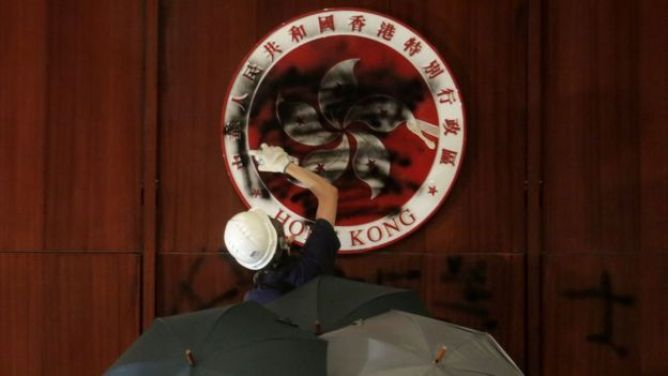The emblem of Hong Kong in the legislative chamber is spray-painted black by one protester, buoyed by three people holding umbrellas behind him.