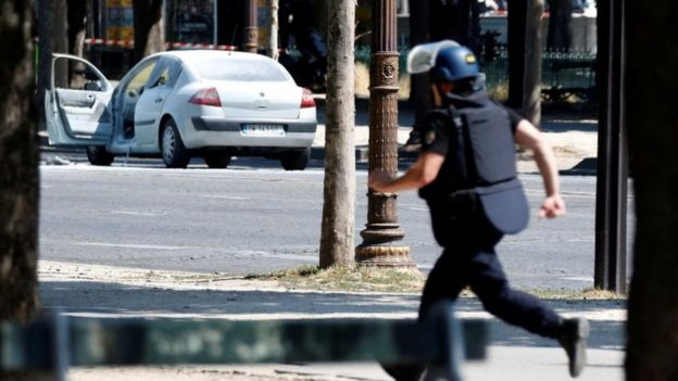 A French gendarme runs past a car on the Champs Elysees avenue after an incident in Paris, France, on 19 June 2017.
