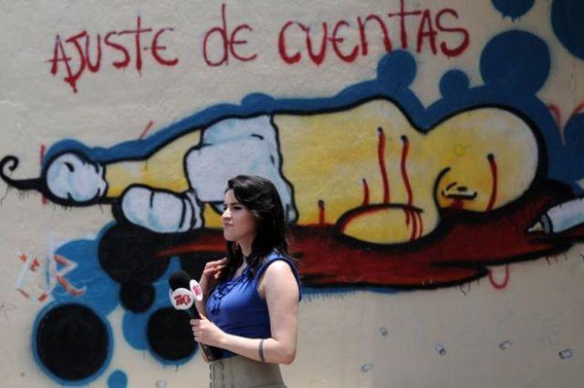 """Periodista frente a un grafiti en el que se lee """"Ajuste de cuentas"""" el 26 de abril de 2013."""