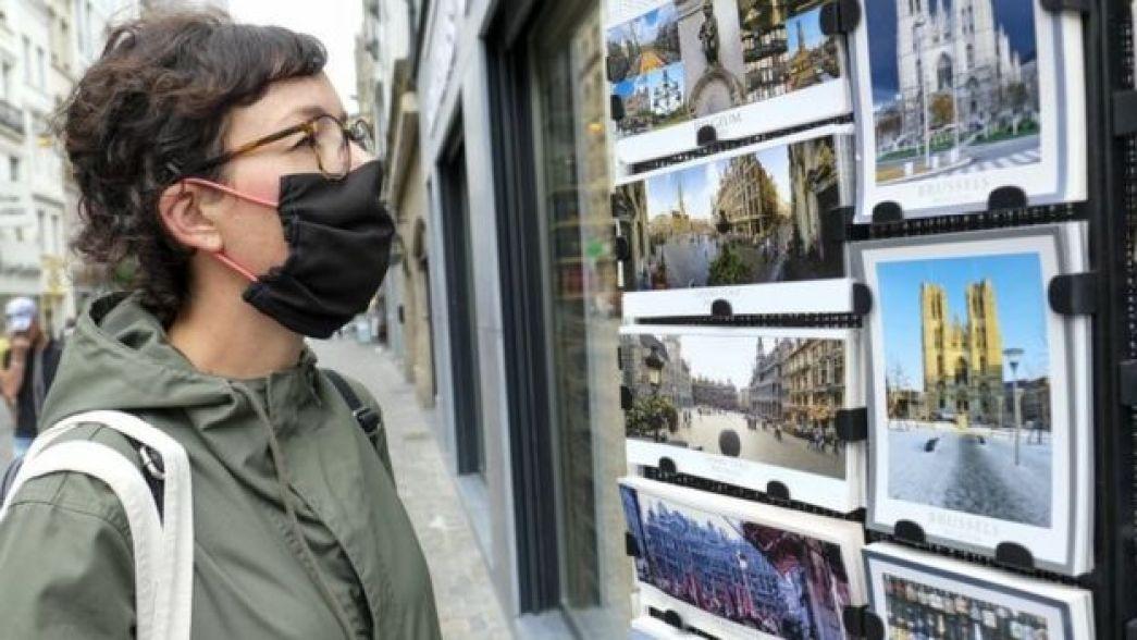 Una mujer mira postales de Bruselas en un escaparate
