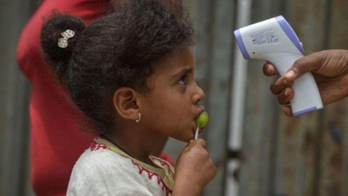 Des agents de vulgarisation sanitaire du ministère de la santé mesurent la tentation d'une jeune fille lors d'un dépistage porte-à-porte pour freiner la propagation du coronavirus COVID-19 à Addis-Abeba, en Éthiopie, le 20 avril 2020