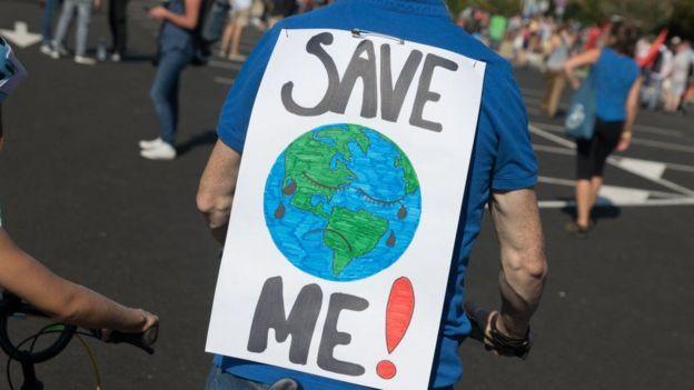 Un hombre con un cartel con un dibujo de la tierra