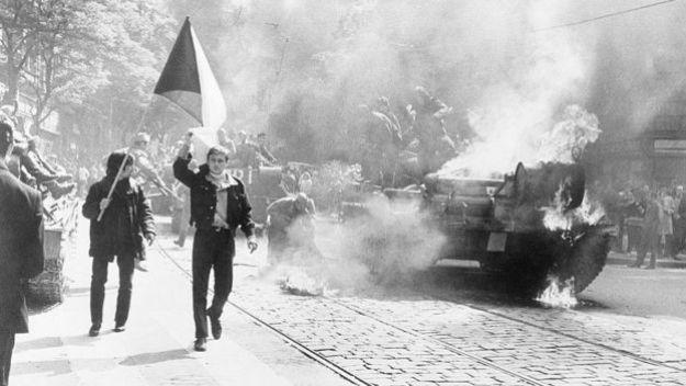 Чешские студенты с флагом возле горящего танка.