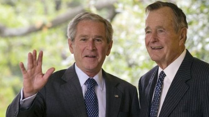 US President George W Bush waves as he leaves the Oval Office with his father, former President George H W Bush - 25 September 2008