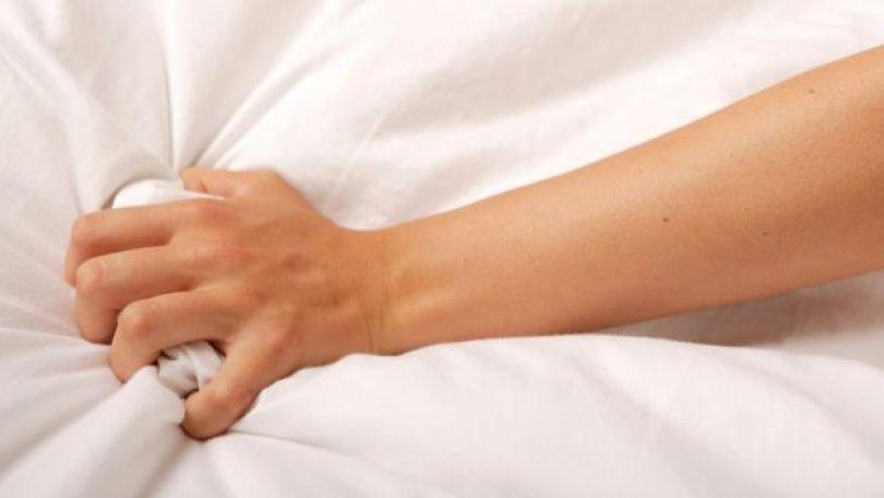 Braço de mulher agarrando o lençol.