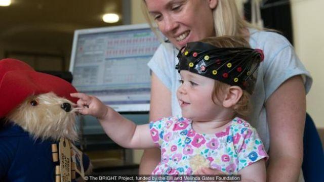 Mulher segura bebê com capacete futurista