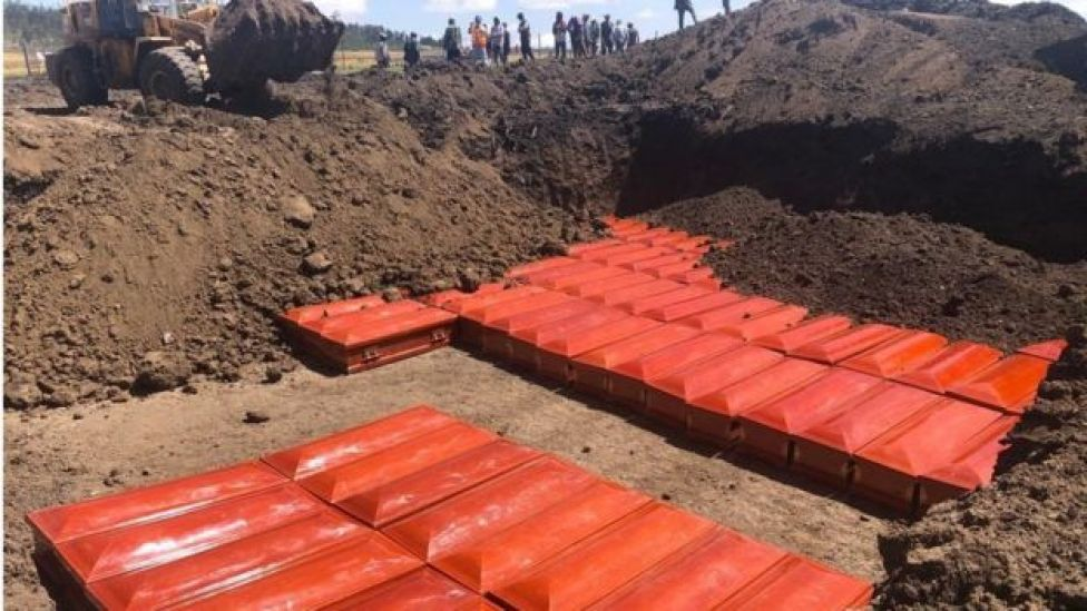 red coffins covered in dirt