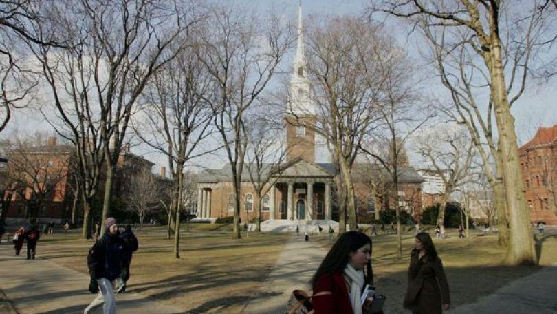 Imagem mostra pessoas caminhando em frente à Universidade de Harvard