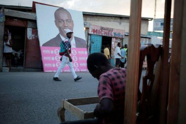 Un hombre camina frente a la pancarta electoral con la foto del candidato Jovenel Moïse en Puerto Príncipe.