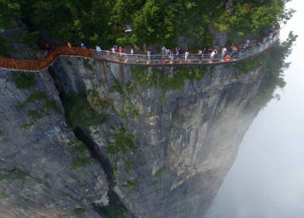 La gente camina por un puente de cristal en la la montaña de Tianmen en el Parque forestal nacional Zhangjiajie, en China.
