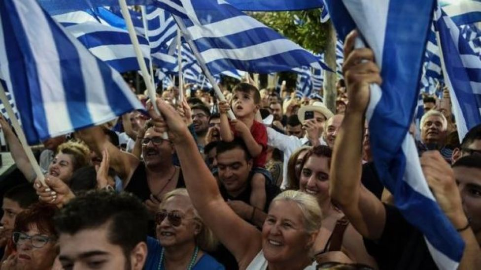 Supporters of Greece's opposition party New Democracy cheer and wave Greek national flags