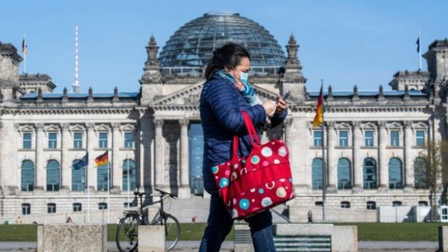 A woman walks past the Reichstag in Berlin in a face mask
