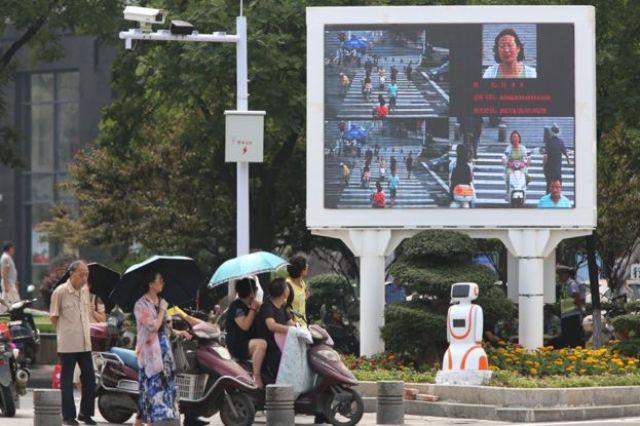 Equipo de reconocimiento facial y una pantalla diseñada para avergonzar a los peatones imprudentes en una concurrida intersección en Xiangyang el 26 de junio de 2017