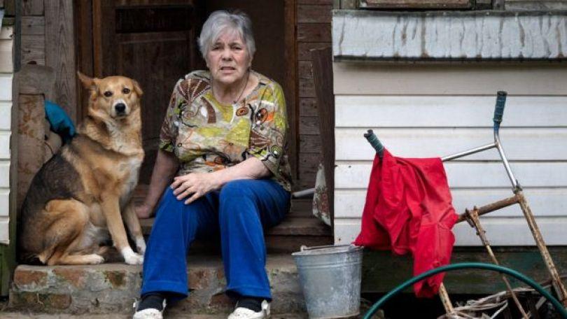 Mulher idosa sentada na porta de casa, com um cachorro