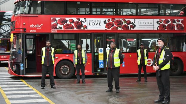 """Staff stand inside Camberwell bus depot in London, during a minute""""s silence to pay tribute to the NHS staff and key workers who have died during the coronavirus outbreak. PA Photo. Picture date: Tuesday April 28, 2020. Transport for London said its underground and bus network will be brought to a halt for the silence as the workforce honours its colleagues."""