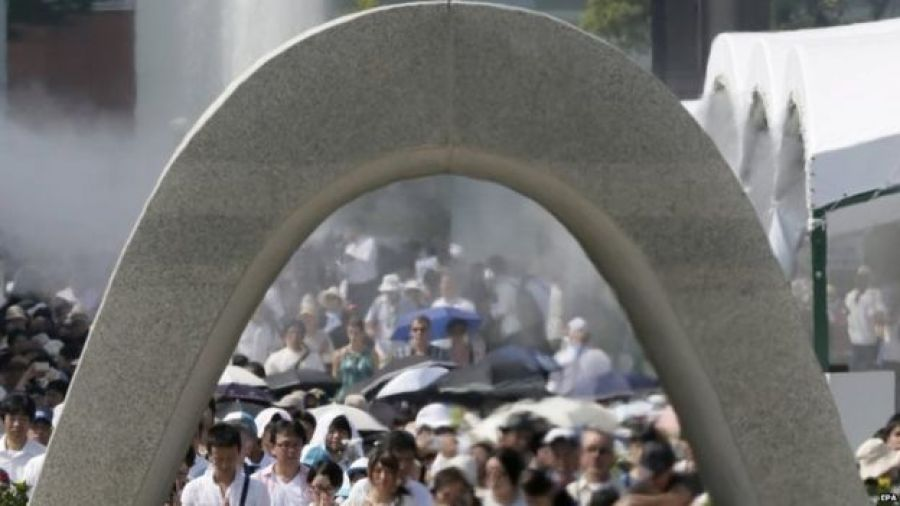 People offer prayers for victims of the atomic bombing in front of a cenotaph at Hiroshima Peace Memorial Park (06 August 2015)
