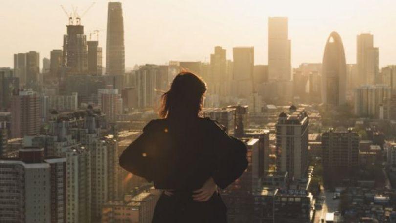 Mulher observa vista a partir do topo de um prédio