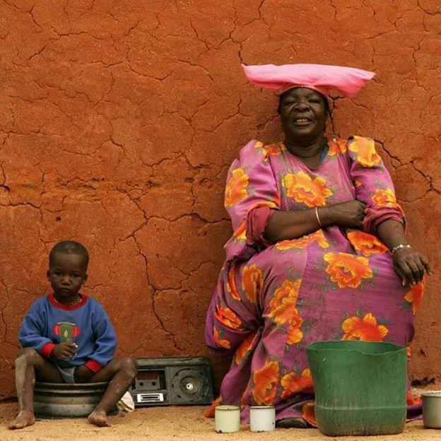Mujer Herero frente a su casa de adobo junto a un niño