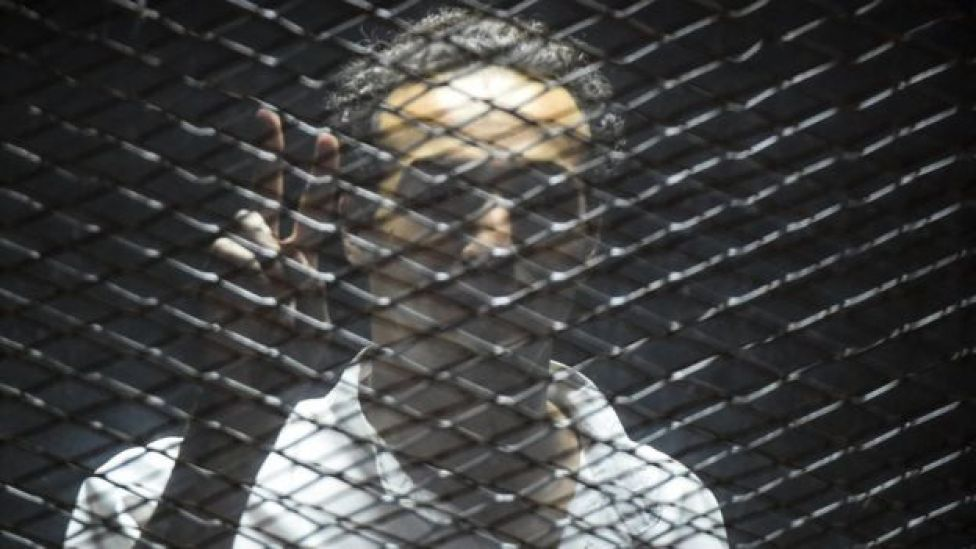 Egyptian photographer Mahmoud Abdel Shakour Abou Zeid, also known as Shawkan, flashes the victory gesture from inside a soundproof glass dock, during his trial in the capital Cairo on July 28, 2018