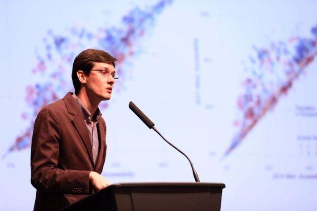 Foto do pesquisador Rafael Pereira com gráficos ao fundo