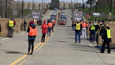 Voluntários com coletes laranja organizam fila de carros que vão receber doação de alimentos