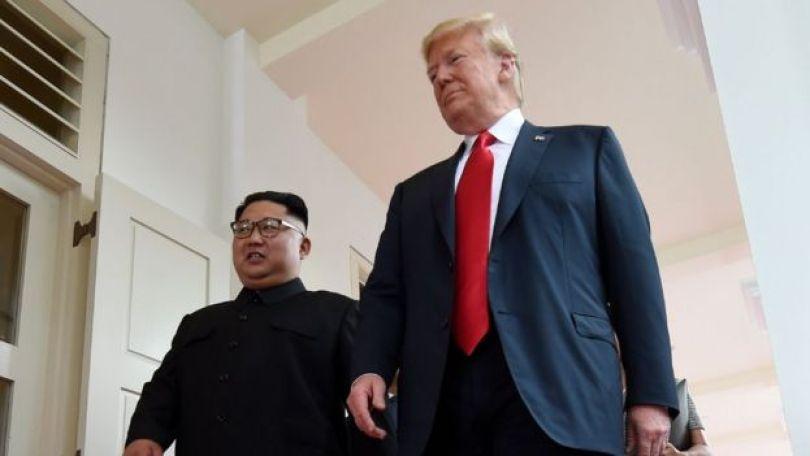 Kim e Trump caminham em direção á reunião individual que tiveram, com a presença somente de tradutores