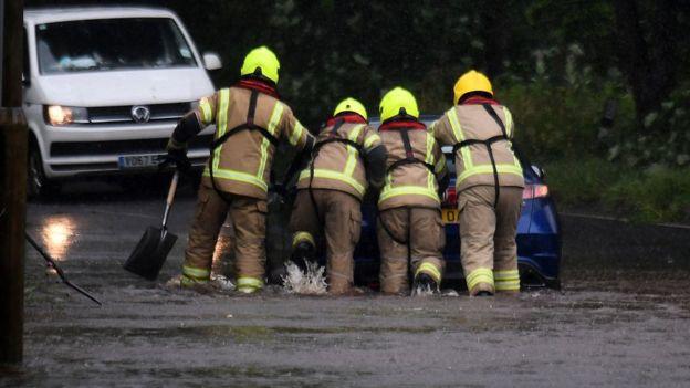 Fire crews help a car out of flood water in Lochwinnoch