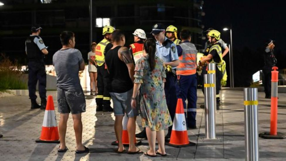 Police talk with evacuated residents from the Opal Tower on Monday