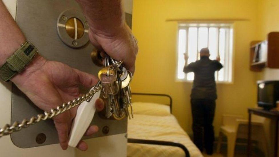 Un détenu non identifié au Royaume-Uni regarde par la fenêtre pendant qu'un gardien de prison l'enferme.