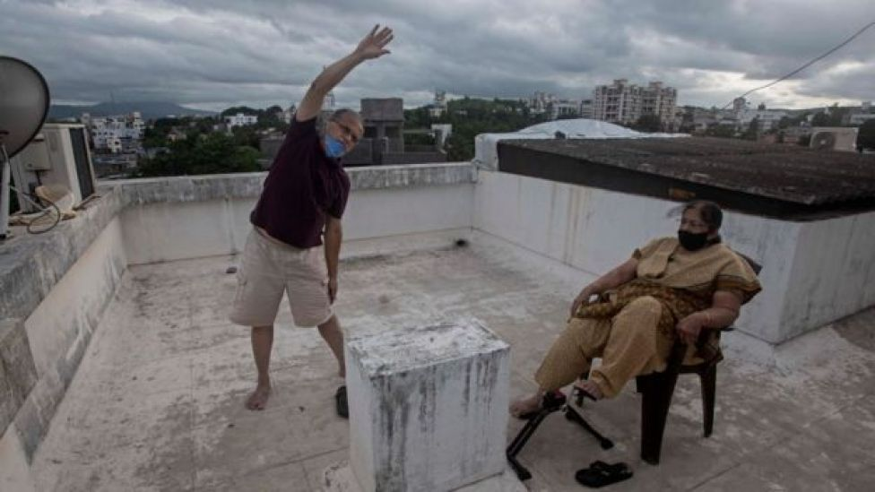 Um homem idoso se exercita em um telhado ao lado de sua esposa em Nova Delhi
