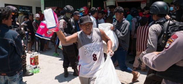 People leave a shop carrying looted goods in Palu